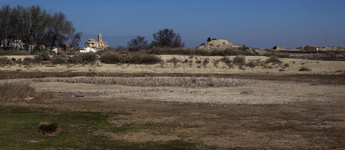 """The church of """"Nuestra Senyora de la Asuncion"""" is seen at the background near a dry pool in Robres village, Huesca, Spain, Tuesday March 13, 2012. Spain is suffering the driest winter in more than 70 years, adding yet another woe for an economically distressed country that can scarcely afford it. Thousands of jobs and many millions of euros could be in jeopardy. (AP Photo/Emilio Morenatti)"""