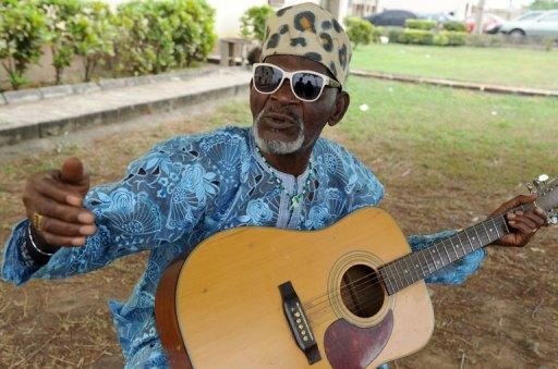 Highlife musician Fatai Rolling Dollar poses with his guitar in Lagos on August 25, 2011