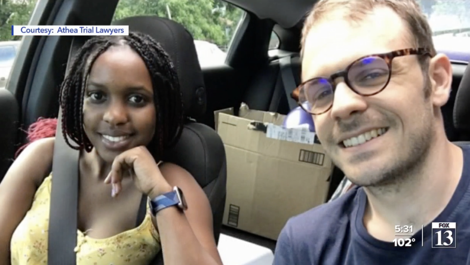 Esther Nakajjigo and her husband Ludo Michaud pose for a photo while sitting in a car.