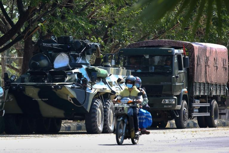 Motorists pass military vehicles near a guesthouse where members of parliament reside, in Myanmar's capital Naypyidaw on February 3, 2021, two days after a military coup