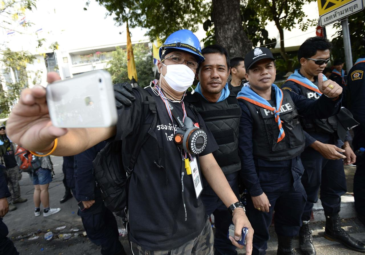 Thai riot police smile as they pose with anti-government protesters after demonstrations are called off outside Government House in Bangkok December 3, 2013. Thailand's government ordered police to stand down and allow protesters into state buildings on Tuesday, removing a flashpoint for clashes and effectively bringing an end to days of violence in Bangkok in which five people have died. REUTERS/Dylan Martinez (THAILAND - Tags: CIVIL UNREST POLITICS)