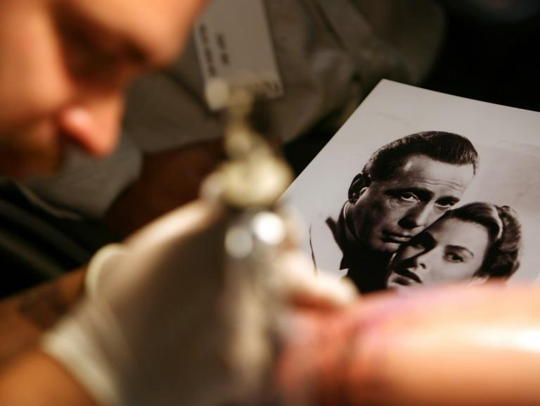"A tattoo artist works from a portrait of Hollywood legends Humphrey Bogart and Ingrid Bergman, who played star-crossed lovers whose union must be sacrificed for the sake of fighting the Nazis, in the movie ""Casablanca"""