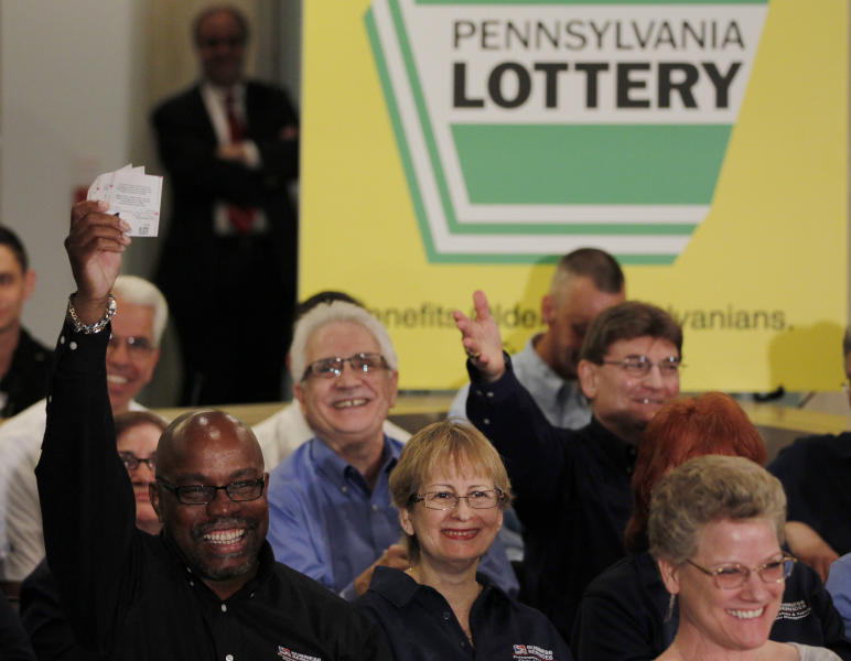 One of the forty plus Southeastern Pennsylvania Transportation Authority employees who won the Powerball lottery displays tickets for an upcoming lottery during a news conference, Friday, May 4, 2012, in Philadelphia. According to Pennsylvania Lottery officials the prize has a cash value of $107.5 million. (AP Photo/Matt Rourke)