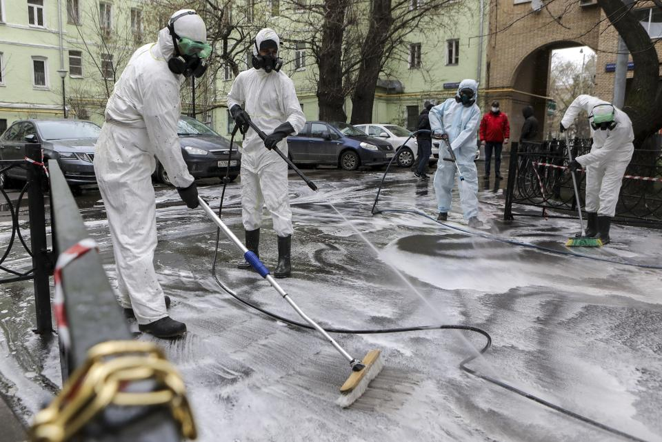 Municipal employees, wearing special suits to protect against coronavirus, disinfect and clean a yard in Moscow, Russia, Saturday, April 18, 2020. Authorities in the Russian capital have ordered most Muscovites who don't work in vital industries to stay home in an effort to stem the spread of the coronavirus. Only visits to nearby stores and pharmacies are allowed, and the lockdown has spurred demand for delivery services. (Sofia Sandurskaya, Moscow News Agency photo via AP)