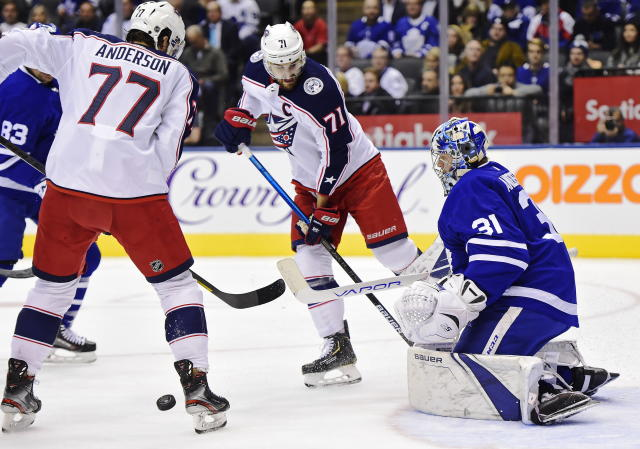Toronto Maple Leafs goaltender Frederik Andersen (31) makes a save as Columbus Blue Jackets right wing Josh Anderson (77) and left wing Nick Foligno (71) look for a rebound during first-period NHL hockey game action in Toronto, Monday, Oct. 21, 2019. (Frank Gunn/The Canadian Press via AP)