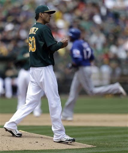 Texas Rangers' Nelson Cruz, background right, runs the bases after hitting a three-run home run off Oakland Athletics' Jesse Chavez, left, in the fifth inning of a baseball game on Wednesday, May 15, 2013, in Oakland, Calif. (AP Photo/Ben Margot)
