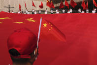 People hold a huge Chinese national flag during a ceremony to mark China's 72nd National Day in Hong Kong Friday, Oct. 1, 2021. (AP Photo/Vincent Yu)