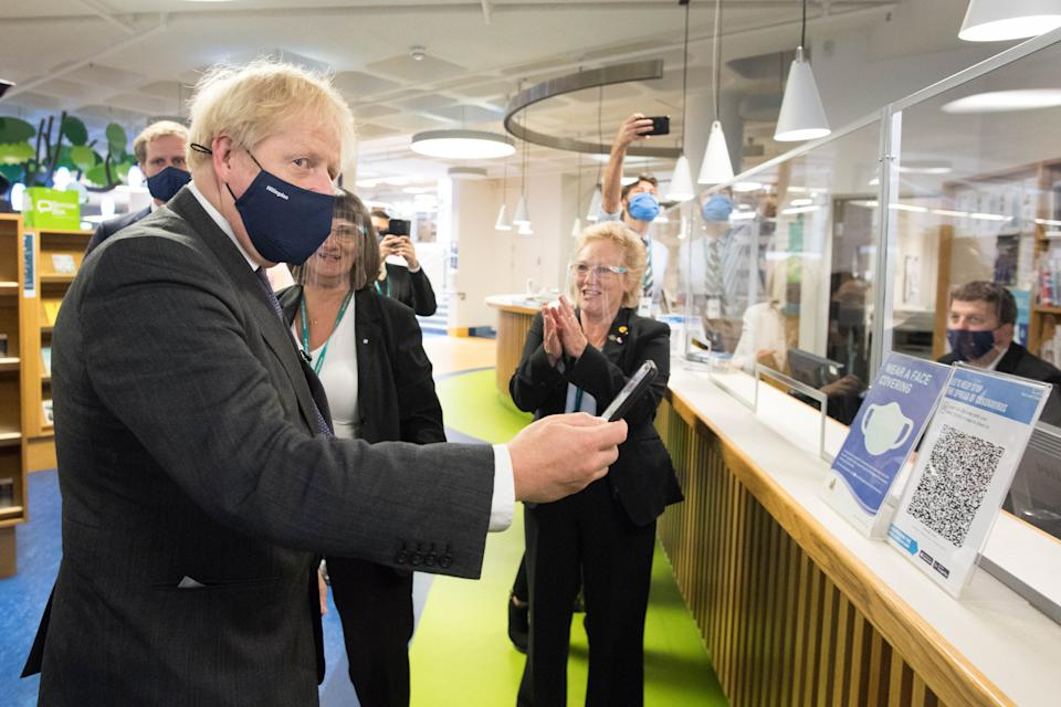 Prime Minister Boris Johnson scans his NHS Coronavirus App at Uxbridge Library during a walkabout where he met shoppers and shopkeepers in his constituency of Uxbridge, west London.