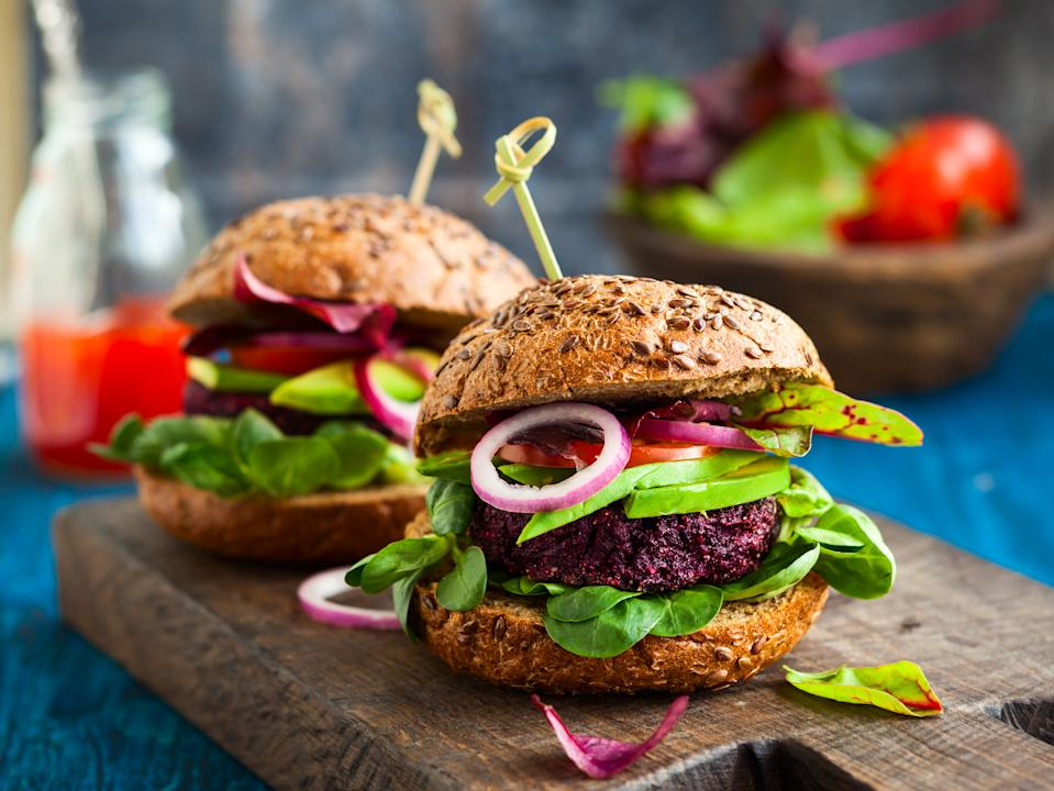Veggie beet and quinoa burger with avocado on the vintage wooden board