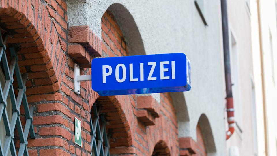 Munich, Bavaria / Germany - Feb 21, 2020: Polizei sign at the facade of a police station (Polizeiinspektion 11, Hochbrückstraße). White letters, blue background. 16:9 panorama. Keepers of law & order.