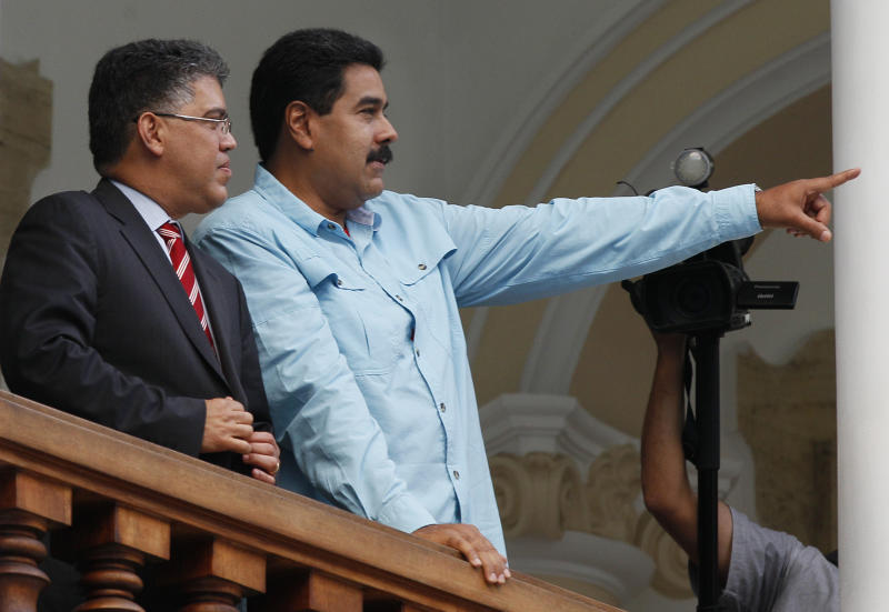 """Venezuela's President Nicolas Maduro, right, and Venezuela's Foreign Minister Elias Jaua, stand on the balcony of the Foreign Ministry after meeting with South Africa's foreign minister, in Caracas, Venezuela, Thursday, Sept.19, 2013. Jaua said Thursday that the United States has prohibited a planned flight by Maduro from passing through U.S. airspace over Puerto Rico. The foreign minister said that the flight had been scheduled to pass over the U.S. territory on Friday on its way to China. He characterized the U.S. action as an """"aggression."""" (AP Photo/Ariana Cubillos)"""