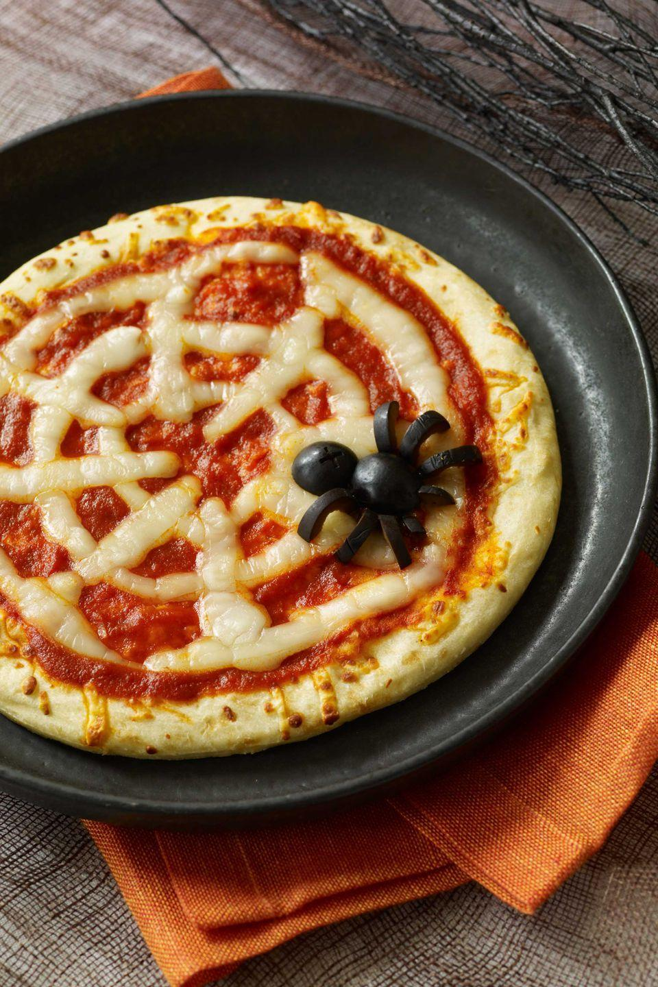 "<p>Serve up a piping hot slice of spookiness with these super-simple pizzas made with pre-baked crust, pizza sauce, strategically placed string cheese and a black olive spider.</p><p><a href=""https://www.womansday.com/food-recipes/food-drinks/recipes/a10838/spiderweb-pizzas-recipe-122166/"" rel=""nofollow noopener"" target=""_blank"" data-ylk=""slk:Get the recipe."" class=""link rapid-noclick-resp""><strong>Get the recipe.</strong></a></p>"