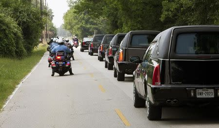 Hearses line up to leave the church following funeral services for members of the Stay family in Spring, Texas July 16, 2014. REUTERS/Daniel Kramer