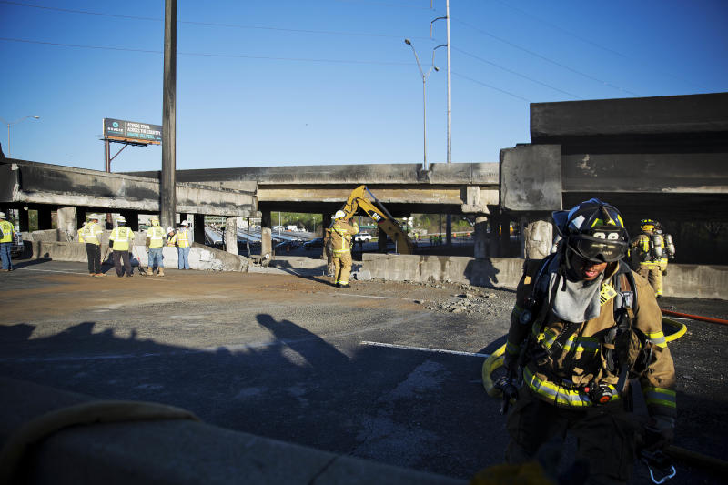 A firefighter works the scene where a section of an overpass collapsed from a large fire on Interstate 85 in Atlanta, Friday, March 31, 2017. Many commuters in some of Atlanta's densely populated northern suburbs will have to find alternate routes or ride public transit for the foreseeable future after a massive fire caused a bridge on Interstate 85 to collapse Thursday, completely shutting down the heavily traveled highway. (AP Photo/David Goldman)