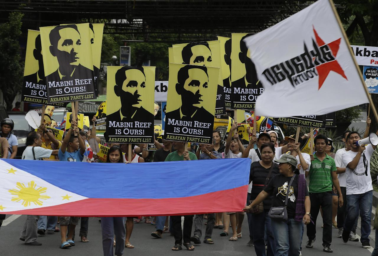Protesters display a Philippine flag and placards while shouting slogans as they march towards the Chinese Consulate at the financial district of Makati city east of Manila Thursday, June 12, 2014, for a rally against recent reclamation and construction at Mabini Reef in the disputed Spratlys group of islands in the South China Sea. The protesters, who are allied with Philippine President Benigno Aquino III, marked the country's Independence Day Thursday, with a protest rally against China's aggressive moves to reclaim land in the South China Sea where the two countries are locked in an escalating territorial dispute.(AP Photo/Bullit Marquez)