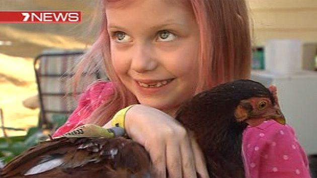 Miette cuddles one of her pet chooks.