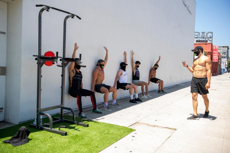 People take an outdoor class at Pylo Fitness, with workout equipment set up on the sidewalk on La Brea Blvd, on August 7 2020, in Los Angeles, California, amid the novel coronavirus pandemic. - California on July 13 drastically rolled back its reopening plans and ordered all indoor restaurants, bars and cinemas to close again. Churches, gyms, shopping malls, hair salons and non-essential offices have had to shut indoor operations in half of state's worst-hit and most densely populated counties, including Los Angeles. (Photo by VALERIE MACON / AFP) (Photo by VALERIE MACON/AFP via Getty Images)