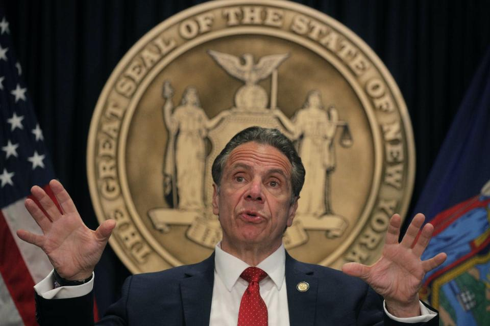 New York Gov. Andrew Cuomo gestures with his hands during a news conference with the seal of New York behind him