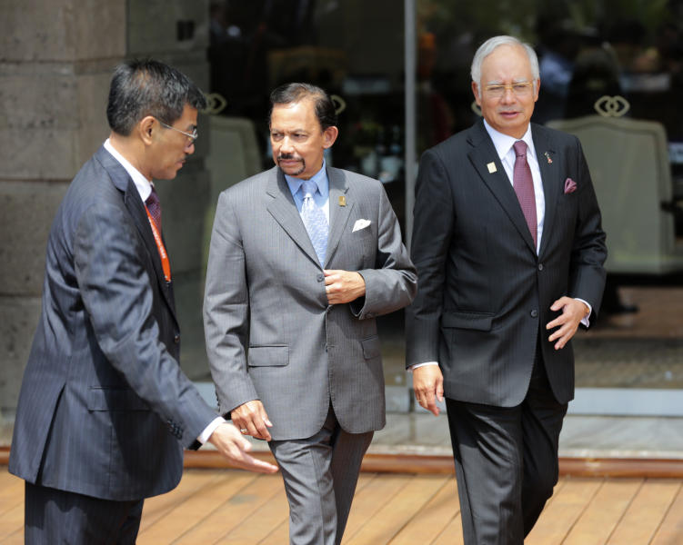 Malaysian Prime Minister Najib Razak, right, and Brunei Sultan Hassanal Bolkiah, center, arrive for a group photo session for the leaders of the Asia-Pacific Economic Cooperation (APEC) forum in Bali, Indonesia, Tuesday, Oct. 8, 2013. (AP Photo/Dita Alangkara)