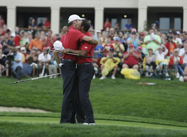 United States' Matt Kuchar and Tiger Woods celebrate after defeating International's Hideki Matsuyama, of Japan, and Adam Scott, of Australia, 1-up in a four-ball match at the Presidents Cup golf tournament at Muirfield Village Golf Club on Saturday, Oct. 5, 2013, in Dublin, Ohio. (AP Photo/Darron Cummings)