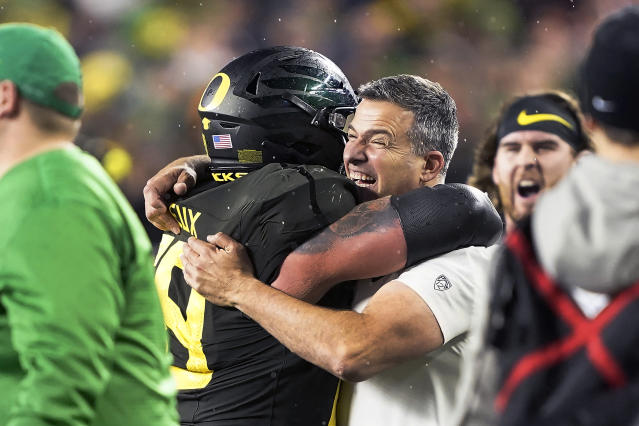 Oregon coach Mario Cristobal, right, celebrates with offensive lineman Shane Lemieux (68) after Oregon defeated Utah 37-15 in and NCAA college football game for the Pac-12 Conference championship in Santa Clara, Calif., Friday, Dec. 6, 2018. (AP Photo/Tony Avelar)