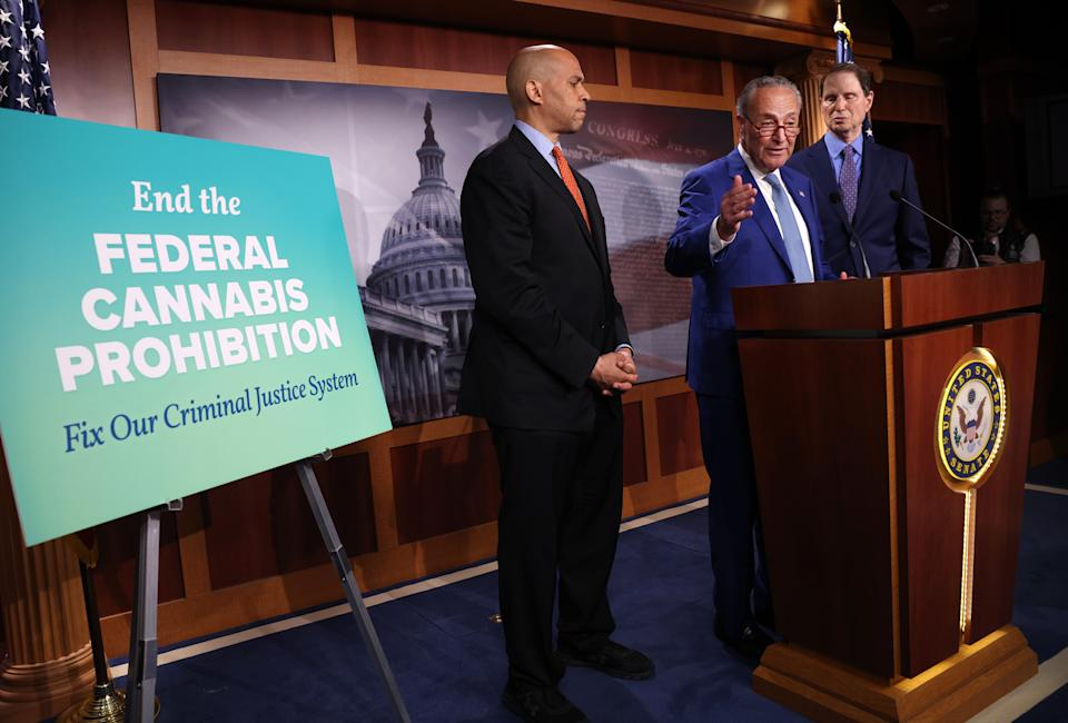 Sen. Chuck Schumer speaks at a podium with two other senators near a sign that reads: End the Federal cannabis Prohibition