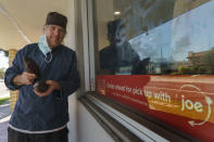 Jeffray Gardner, the owner of Marsatta Chocolate holds cacao fruit pods outside his flagship store in Torrance, Calif., Sunday, March 28, 2021. Restaurants and delivery companies remain uneasy partners, haggling over fees and struggling to make the service profitable for themselves and each other. Gardner says he probably loses money on the one or two delivery orders he gets each day. But he's still happy to work with delivery companies because they help him reach a wider audience. (AP Photo/Damian Dovarganes)
