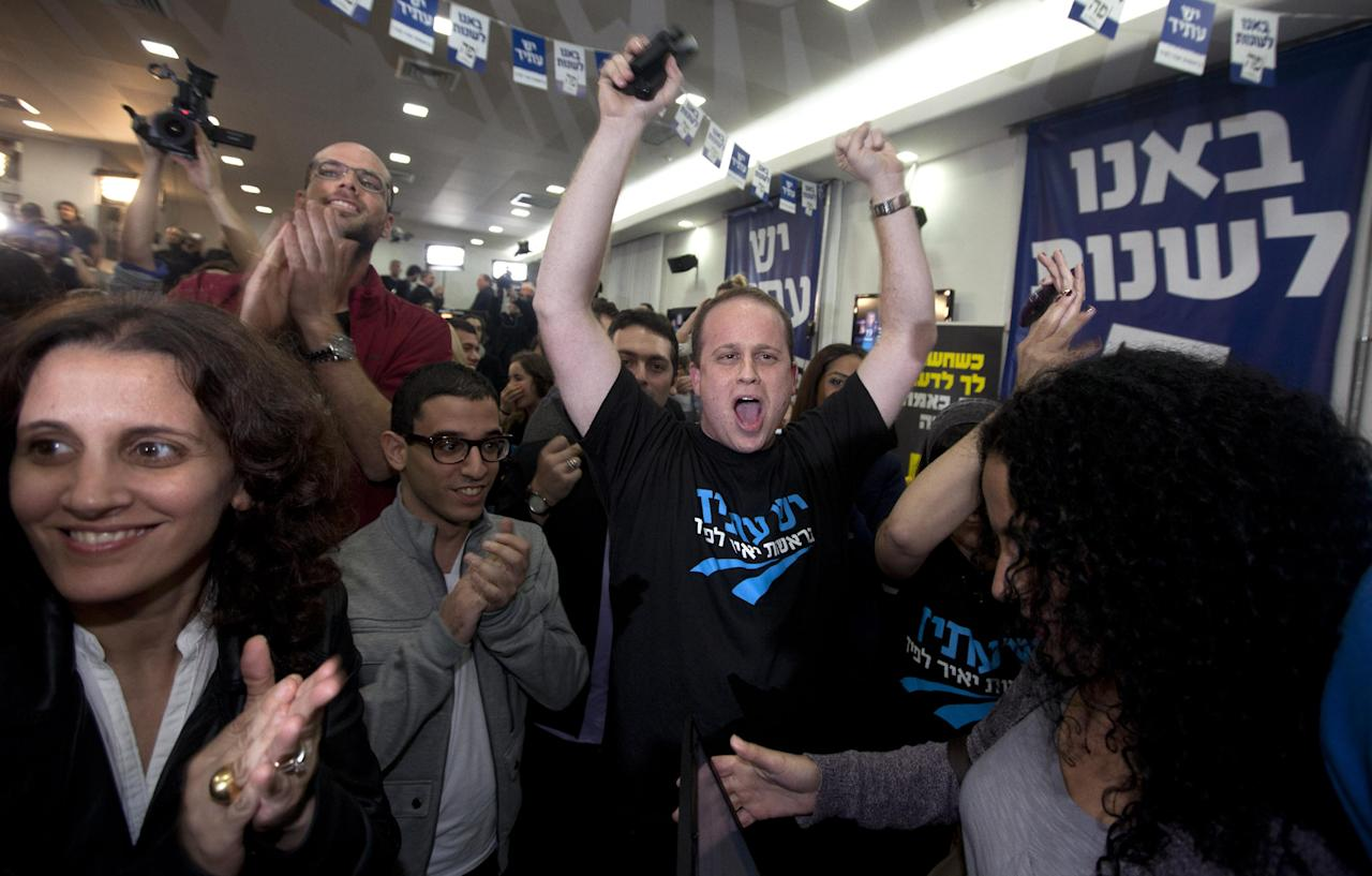 """Supporters of Yair Lapid and his """"Yesh Atid"""" party celebrate election results in Tel Aviv, Tuesday, Jan. 22, 2013. The party, formed just over a year ago, out did forecasts by far and are predicted to capture as many as 19 seats, becoming parliament's second-largest party, after Netanyahu's Likud-Beiteinu bloc, which won 31, according to the exit polls. (AP Photo/Sebastian Scheiner)"""