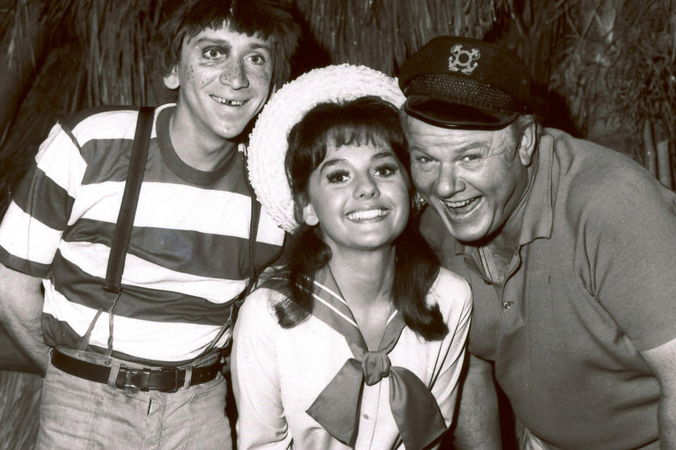 "FILE - In this 1965 file photo, Dawn Wells, center, poses with fellow cast members of ""Gilligan's Island,"" Bob Denver and Alan Hale Jr., in Los Angeles. Wells, who played the wholesome Mary Ann on the 1960s sitcom ""Gilligan's Island,"" has died. Her publicist says Wells died early Wednesday, Dec. 30, 2020, in Los Angeles, of causes related to COVID-19. (AP Photo/File)"