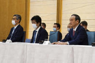 ADDS NAMES OF PARTICIPANTS - Japanese Prime Minister Yoshihide Suga, right, with Dr. Shigeru Omi, left, who heads the government taskforce and Norihisa Tamura, center, Minister of Health, Labor and Welfare, attends the government task force meeting for the COVID-19 measures at the prime minister's office Friday, April 9, 2021, in Tokyo. Japan announced Friday that it will raise the coronavirus alert level in Tokyo to allow tougher measures to curb the rapid spread of a more contagious variant ahead of the Summer Olympics. (AP Photo/Eugene Hoshiko, Pool)