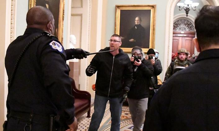 Police confront Trump supporters on the second floor of the US Capitol near the entrance to the Senate after they breached security defenses.
