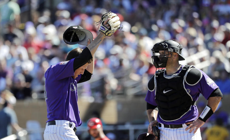 Colorado Rockies starting pitcher Kyle Freeland, left, wipes his face as he talks with catcher Chris Iannetta in the fifth inning of a spring training baseball game against the Cincinnati Reds, Monday, March 18, 2019, in Scottsdale, Ariz. (AP Photo/Elaine Thompson)