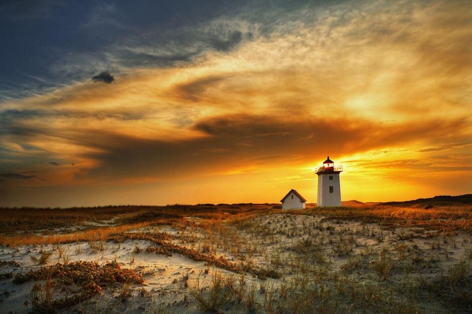 <p>The setting sun casts a golden hue across the sky above Wood End lighthouse in Provincetown.</p>