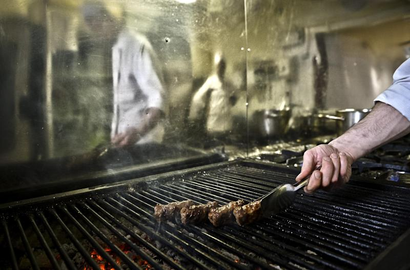 "A chef grills 'mici', the Romanian version of a Turkish dish, spicy grilled sausages, popular across the Balkans, in a restaurant in Bucharest, Romania, Saturday, Feb. 15, 2014. Officials in Brussels have agreed that spicy ""mici"", grilled meat bullet shaped delicacies which rely on a pinch of bicarbonate of soda for their distinctive succulent flavor and puffy texture will be permitted under European Union rules, the Romanian Meat Association says.(AP Photo/Andreea Alexandru/Mediafax) ROMANIA OUT"