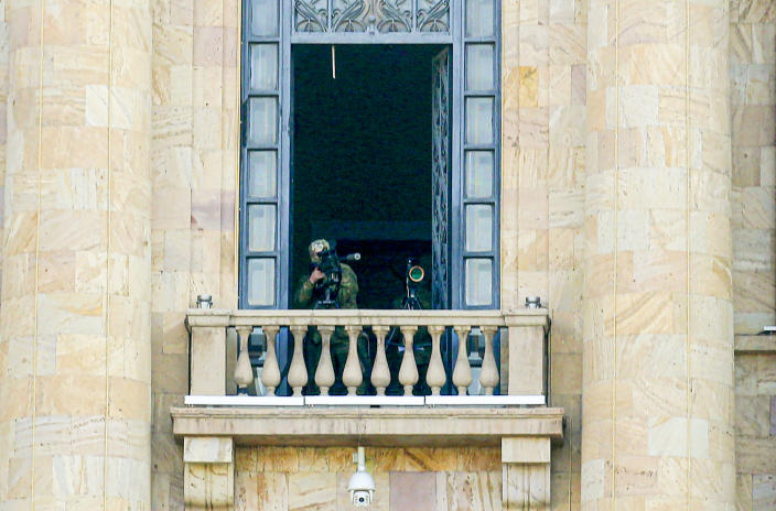 A security agent points a sniper rifle from a window of the Parliament building as opposition demonstrators rally to pressure Armenian Prime Minister Nikol Pashinyan to resign in Yerevan, Armenia, Wednesday, March 3, 2021. Armenia's prime minister has scored a point in his spat with the top military brass, advancing his motion to fire the country's top military officer. A political crisis sparked by Armenia's defeat in the conflict with Azerbaijan over the Nagorno-Karabakh region escalated last week when the military's General Staff demanded the resignation of Prime Minister Nikol Pashinyan following his move to dismiss a top general. (Hrant Khachatryan/PAN Photo via AP)