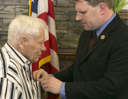 World War II veteran Faulkner is presented the Purple Heart by U.S. Representative Maffei during a ceremony in Auburn, New York