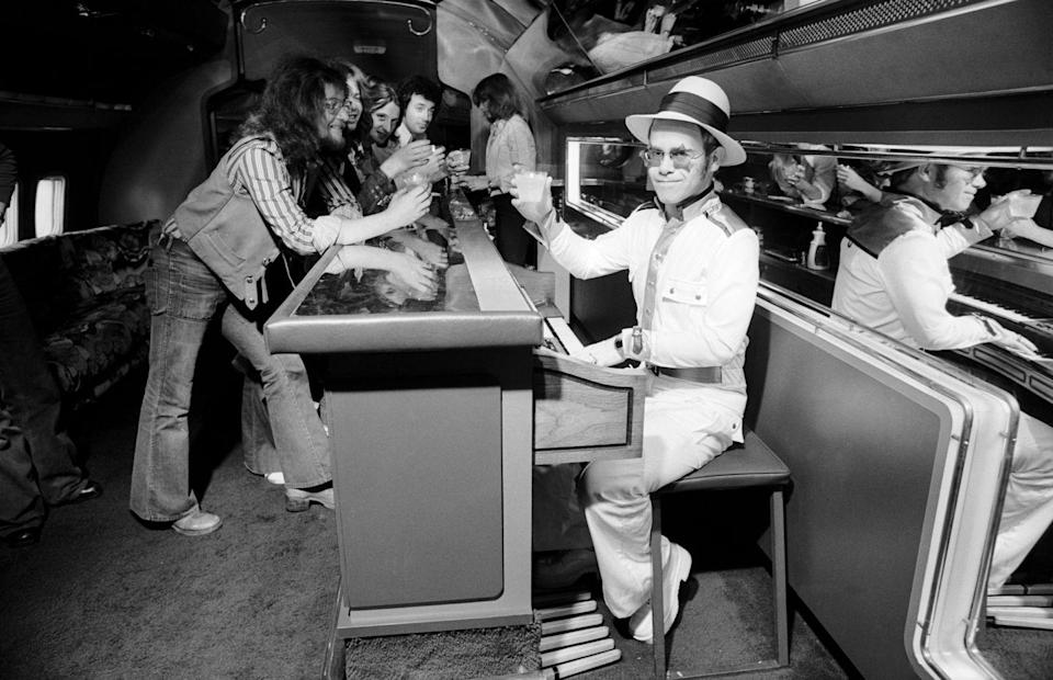 <p>Elton John travels on his 1974 U.S. tour on a private jet complete with a piano bar. </p>