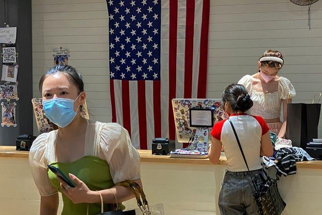 A woman wearing a face mask visits a fashion boutique in Beijing