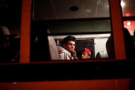 A migrant, part of a caravan of thousands traveling from Central America en route to the United States, eats food in a bus while during a stop to wait for another bus to undergo repairs, on its way to Mexicali, on a shoulder of a highway in Sonoyta, Mexico November 17, 2018. REUTERS/Kim Kyung-Hoon