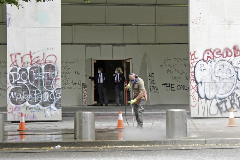 FILE - In this July 8, 2020, file photo, a worker washes graffiti off the sidewalk in front of the Mark O. Hatfield Federal Courthouse in downtown Portland, Ore., as two agents with the U.S. Marshals Service emerge from the boarded-up main entrance to examine the damage. Oregon's largest city is in crisis as violent protests have wracked downtown for weeks. The mayor can't bring the council along on cracking down because of very liberal council members and no matter what he does, the city gets sued anyway. (AP Photo/Gillian Flaccus, File)
