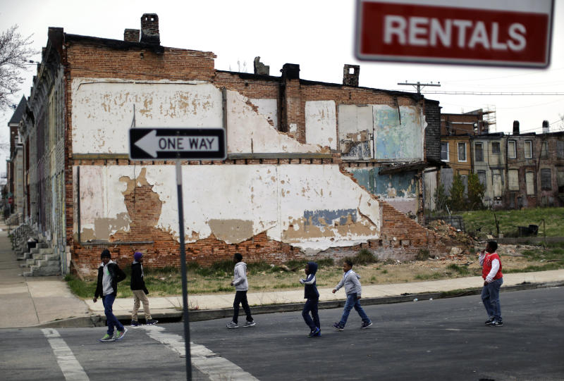 FILE - In this April 4, 2013 file photo, a group of boys walk past a partially collapsed row house in Baltimore. The nation's poverty rate stood still at 15 percent in 2012, the sixth straight year that it has failed to improve. The Census Bureau reported Tuesday, Sept. 17, 2013, that 46.5 million Americans were living in poverty in 2012.. (AP Photo/Patrick Semansky, File)