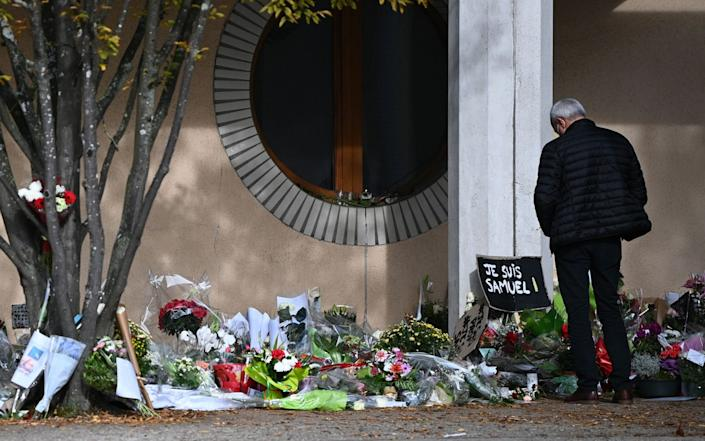 A man looks at flowers layed outside the Bois d'Aulne secondary school in homage to slain history teacher Samuel Paty - AFP