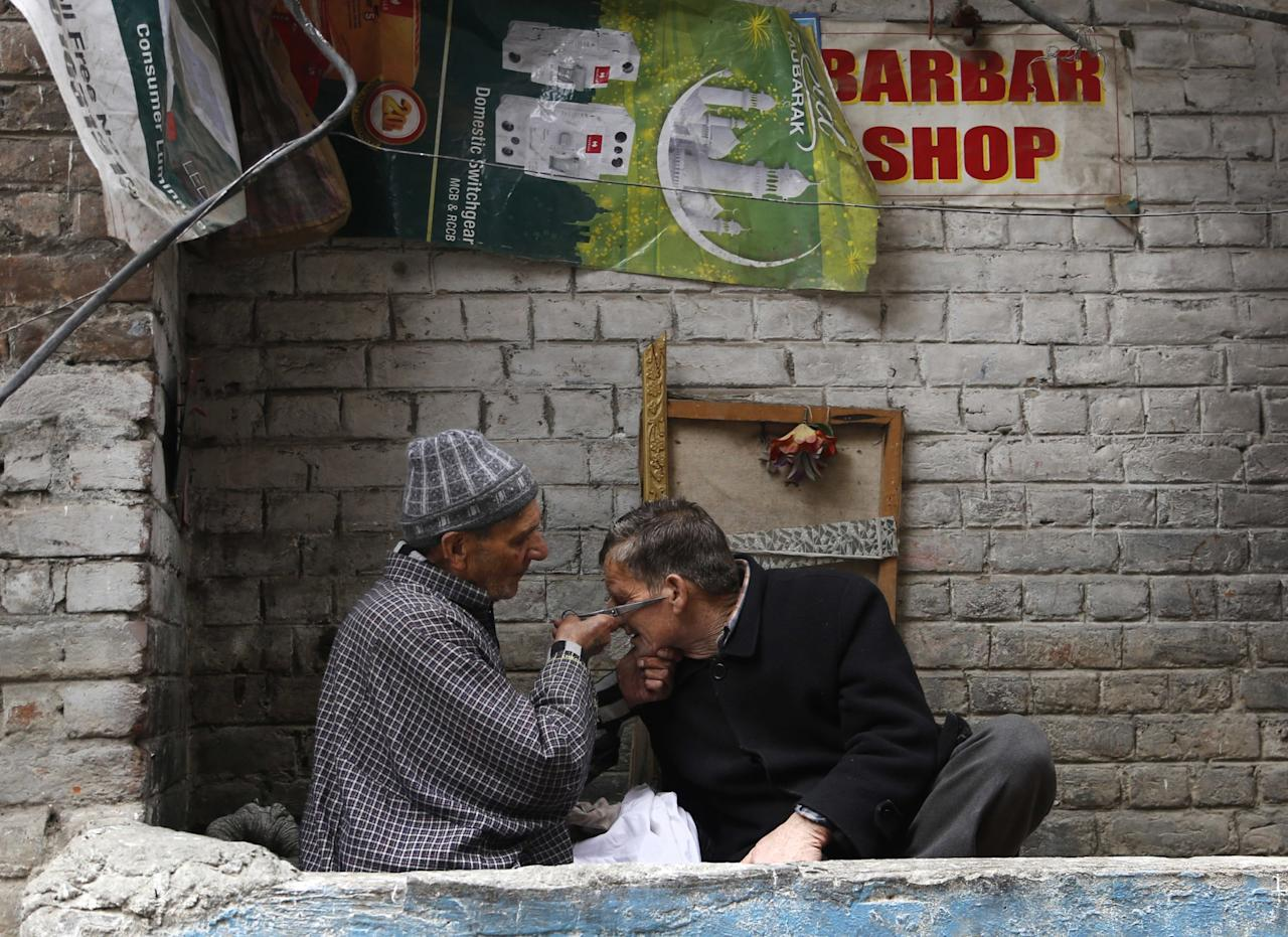 <p>A Kashmiri roadside barber attends to his customer in Srinagar, Thursday, March 16, 2017. Roadside barbers are found across India, offering a shave for as little as 10 Rupees (US$ 0.17). (AP Photo/Mukhtar Khan) </p>