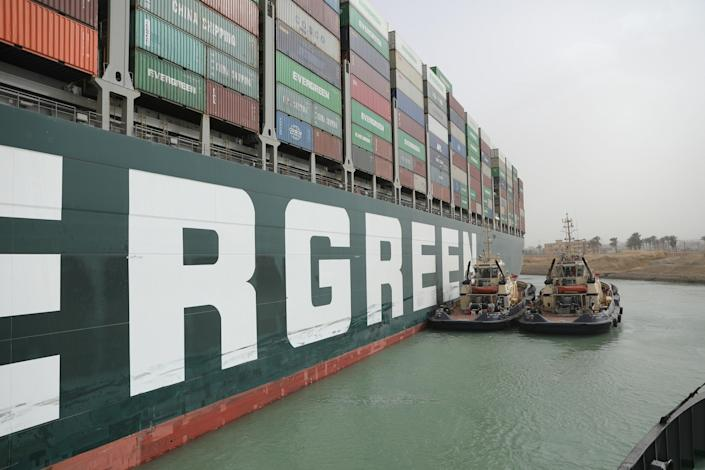 An image released on March 25, 2021 by Egypt's Suez Canal Authority shows tug boats alongside the hull of the MV Ever Given container ship, which was stuck across the canal for a third day. / Credit: Suez Canal Authority