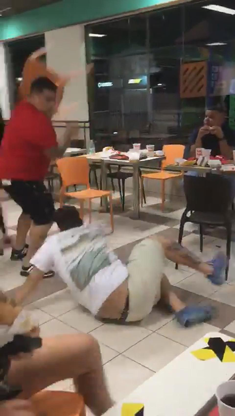 A man holds a chair up during a brawl in McDonald's.