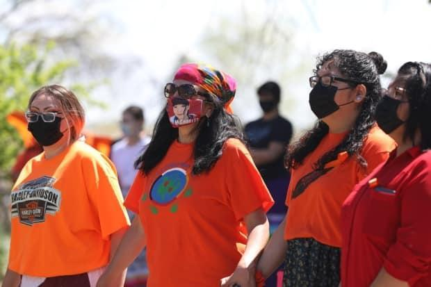 A group of women joins hands during a prayer vigil at the on the grounds of the former Muskowekwan Indian Residential School. (Mickey Djuric/CBC - image credit)