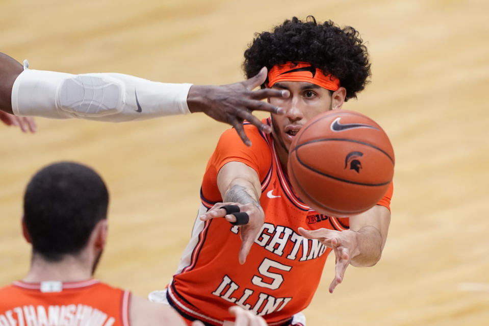 Illinois guard Andre Curbelo (5) passes to forward Giorgi Bezhanishvili during the first half of an NCAA college basketball game against Michigan State, Tuesday, Feb. 23, 2021, in East Lansing, Mich. (AP Photo/Carlos Osorio)
