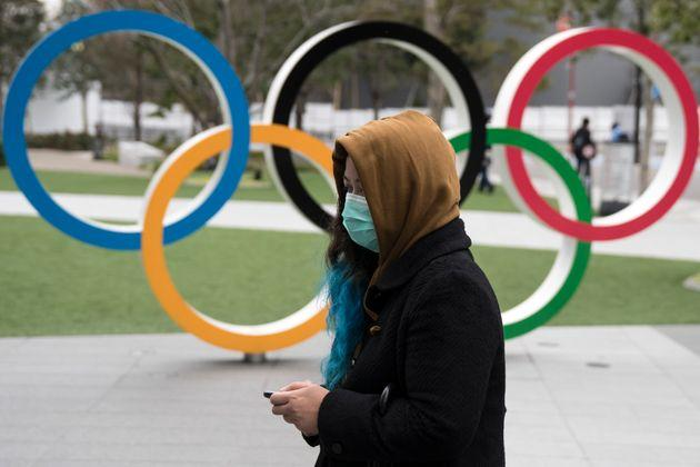 A woman wearing a face mask walks past the Olympic rings in front of the new National Stadium in Tokyo, Japan.