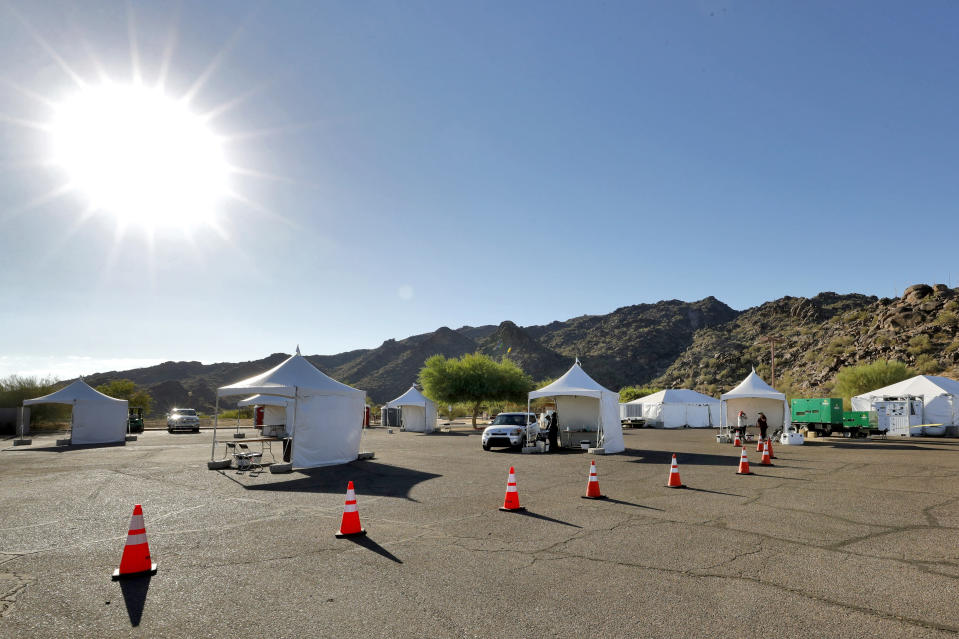 Just one vehicle of people are tested for the COVID-19 Coronavirus Tuesday, July 28, 2020 at South Mountain Park in Phoenix as other testing tents sit idle. It was the last day of a 12-day blitz aimed at bringing tens of thousands of COVID-19 tests to underserved Latino communities in Phoenix but only 14,000 of some 55,000 tests were administered at the park and the western neighborhood of Maryvale, leaving more than 40,000 COVID-19 test kits unused. (AP Photo/Matt York)