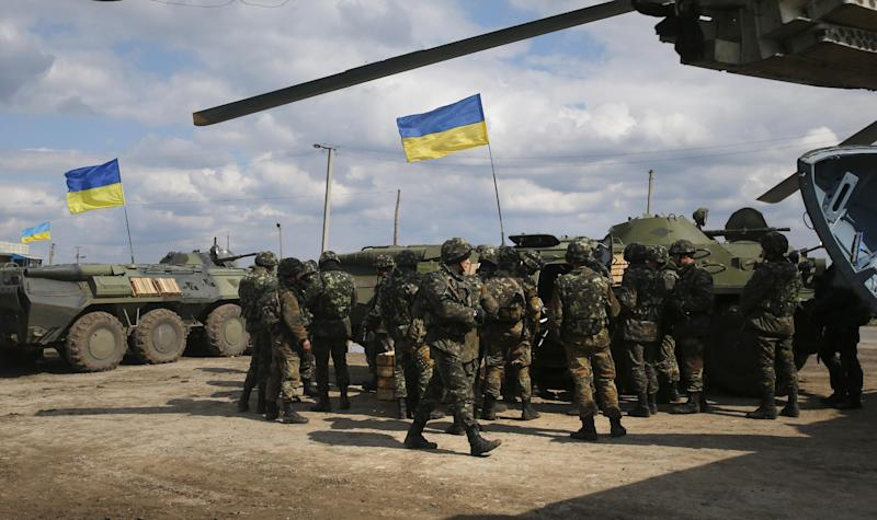 Ukrainian Army troops receive munitions at a field on the outskirts of Izyum, Eastern Ukraine, Tuesday, April 15, 2014. An Associated Press reporter saw at least 14 armored personnel carriers with Ukrainian flags, one helicopter and military trucks parked 40 kilometers (24 miles) north of the city on Tuesday. (AP Photo/Sergei Grits)